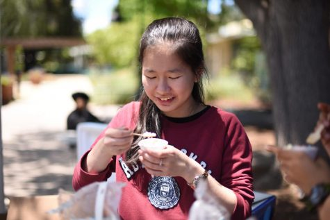 Secretary Helen Li (10) enjoys a cone of Dippin Dots as she waits for students to stop by and purchase some ice cream. By the end of lunch, the students sold out of everything but the Rainbow and Banana Split flavors.
