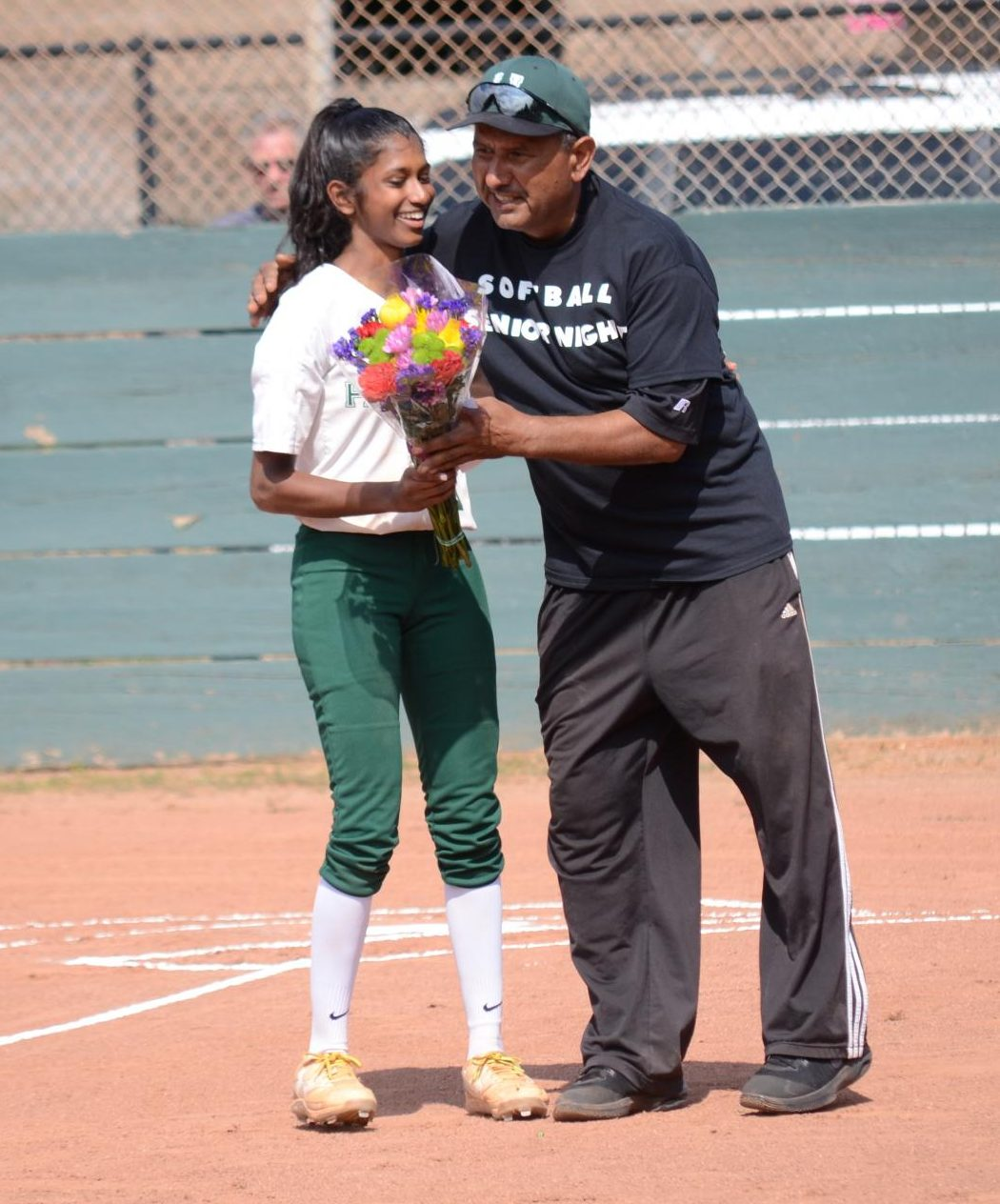 Anika Rajamani (12) receives a bouquet from coach Raul Rios ahead of the game. The girls won the game 23-22.