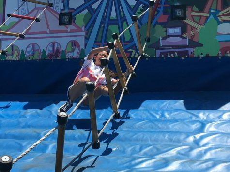 "Angela Gao (9) tries to maintain her balance on a ladder course. ""I was really unsure about roller coasters last year,"" she said. ""This time, I went on Railblazer, and it was super fun."""