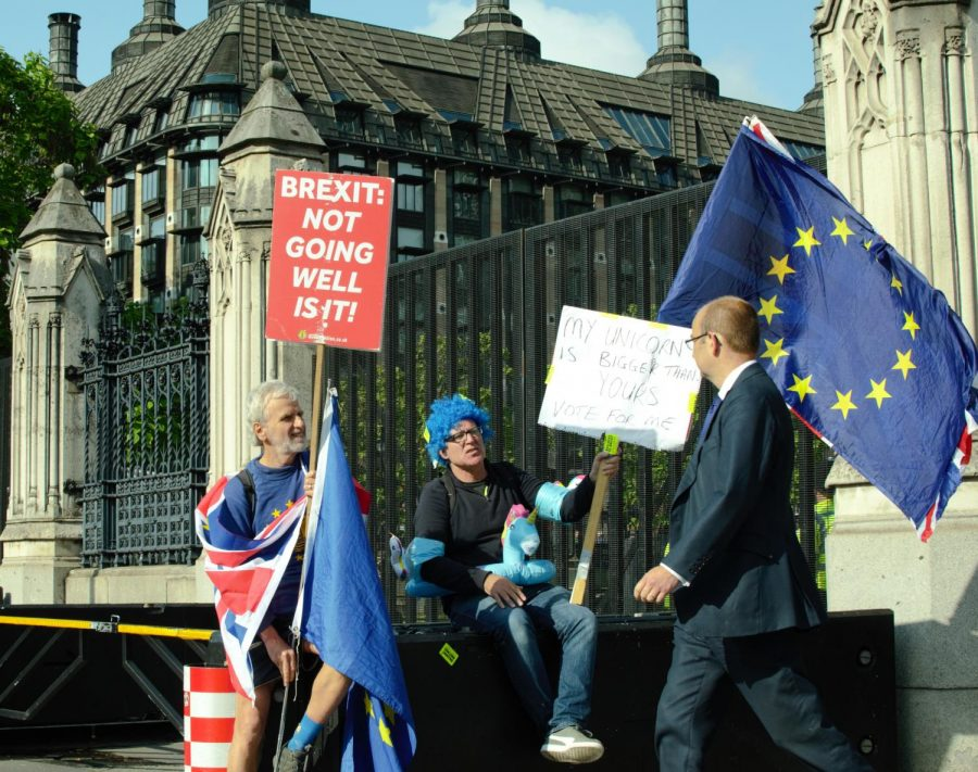 Two people with signs against with messages against Brexit, shout at a member of parliament walking out the The Palace of Westminster. Theresa May, the Prime Minister of Britain, lost in the House of Commons on January 15, 2019, over her deal to leave the European Union.