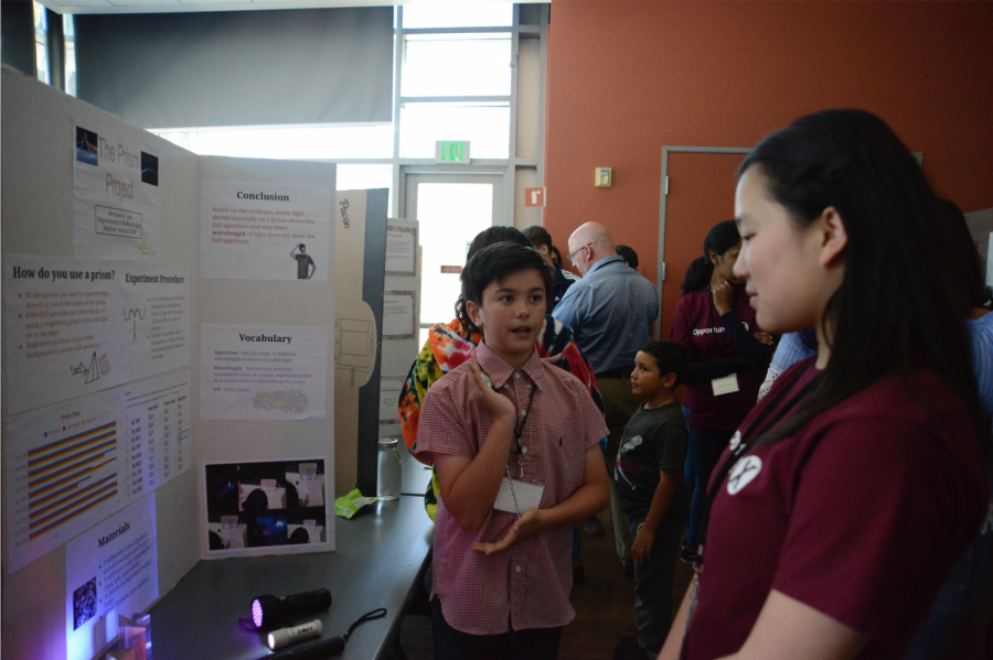 Middle schooler Ben Lee explains his project to Alice Feng (9). He explored the properties of prisms.
