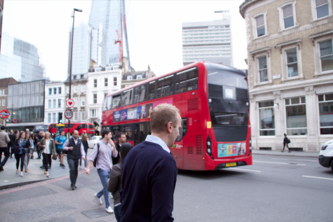 A Londoner motions to cross to the other sidewalk as a cherry red double decker rushes down the busy street.