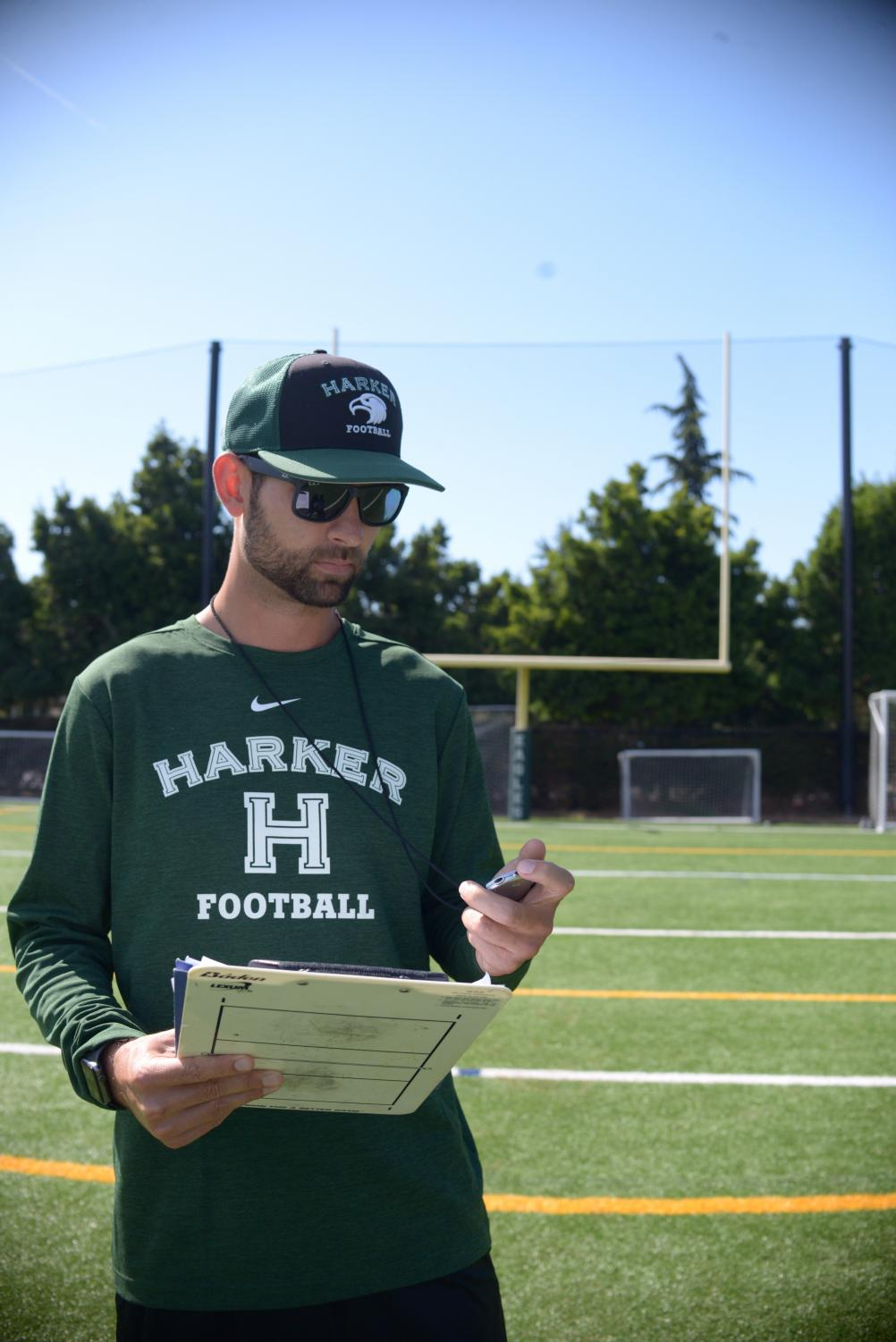 Lorem Powers looks at his stopwatch during practice while holding a clipboard in his other hand.