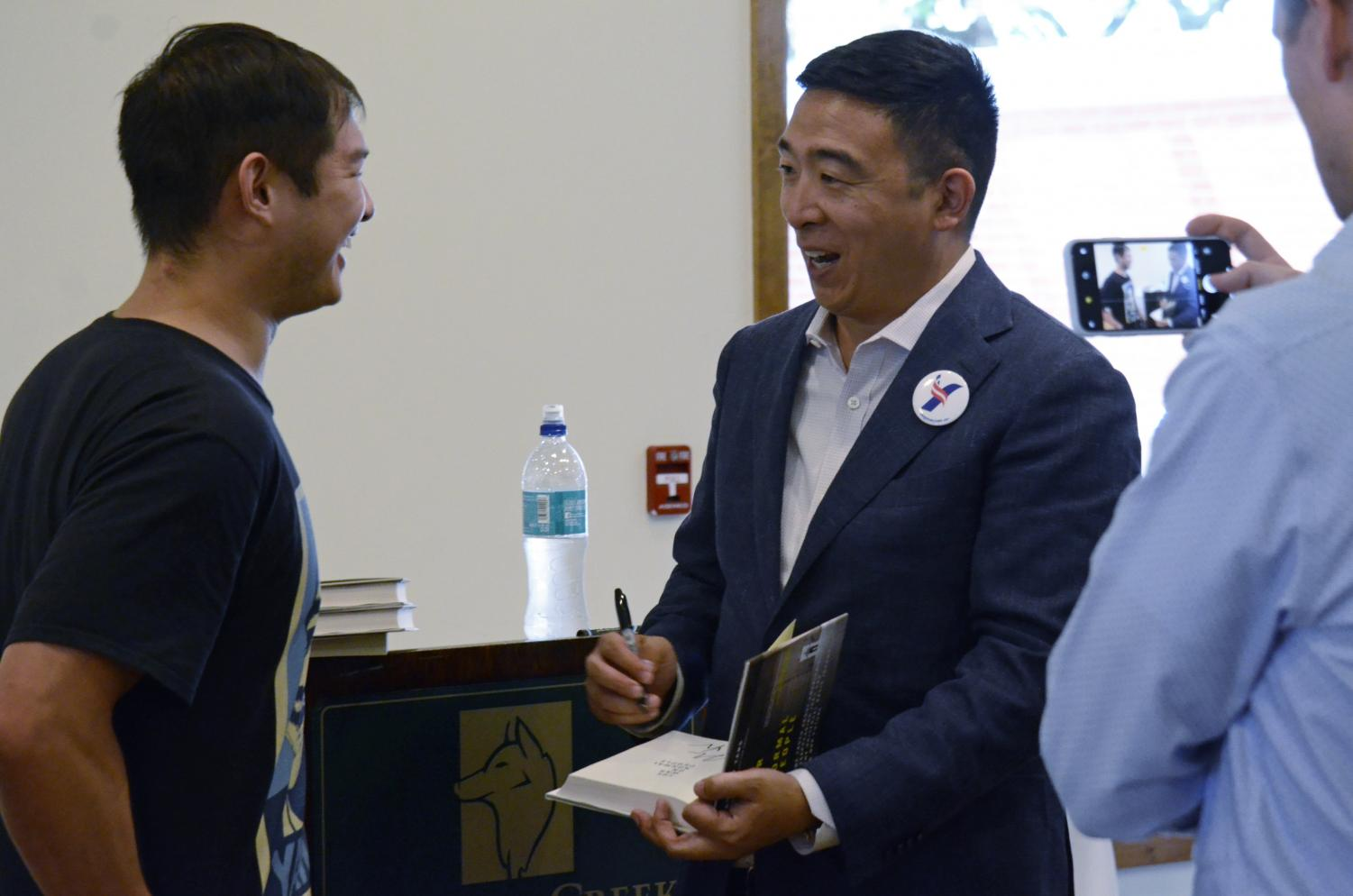 Yang+signs+a+copy+of+his+book+The+War+on+Normal+People+for+a+supporter+while+his+campaign+manager+Zach+Graumann+snaps+a+picture.+