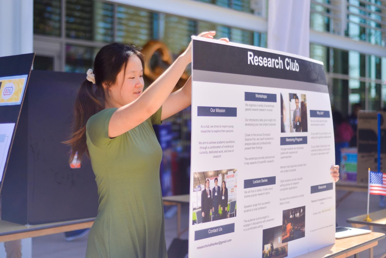 Cynthia+Chen+%2812%29+readjusts+the+board+for+Research+Club+at+Club+Fair+today+during+lunch.+Club+Fair+featured+a+variety+of+student+organizations%2C+ranging+from+STEM+to+business+to+student+activism+groups%2C+and+invited+students+to+sign+up+for+clubs+that+aligned+with+their+interests.+