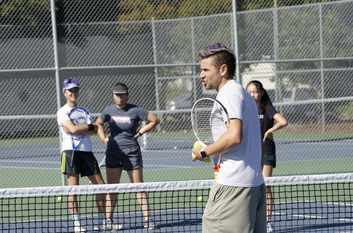 Assistant+coach+John+Paul+Fruttero+talks+to+the+girls+tennis+team%2C+going+over+a+specific+drill.+%E2%80%9CIt%E2%80%99s+a+lot+of+work%2C+because+we+have+practice+every+day+for+two+hours%2C%E2%80%9D+freshman+Alissa+Huda+said+of+tennis+practices.+%E2%80%9CBut+%5Bthere%E2%80%99s%5D+been+a+lot+of+team+bonding%2C+and+%5Bwe+have+become%5D+a+lot+closer.%E2%80%9D+