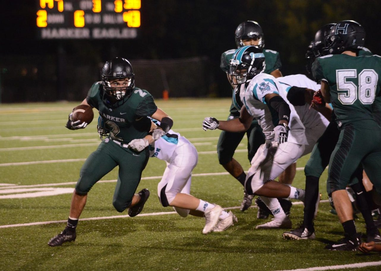 Running back Devin Keller (12) evades a defensive player as he carries the ball downfield during the Eagles matchup against Burton High last Friday. The Eagles lost 57-22.