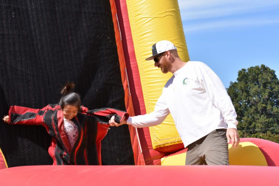 Director of Sports Medicine and Sports Performance Jaron Olson helps a middle school student off of the velcro wall. This new attraction was one of many that were introduced at this year's Family & Alumni Picnic.