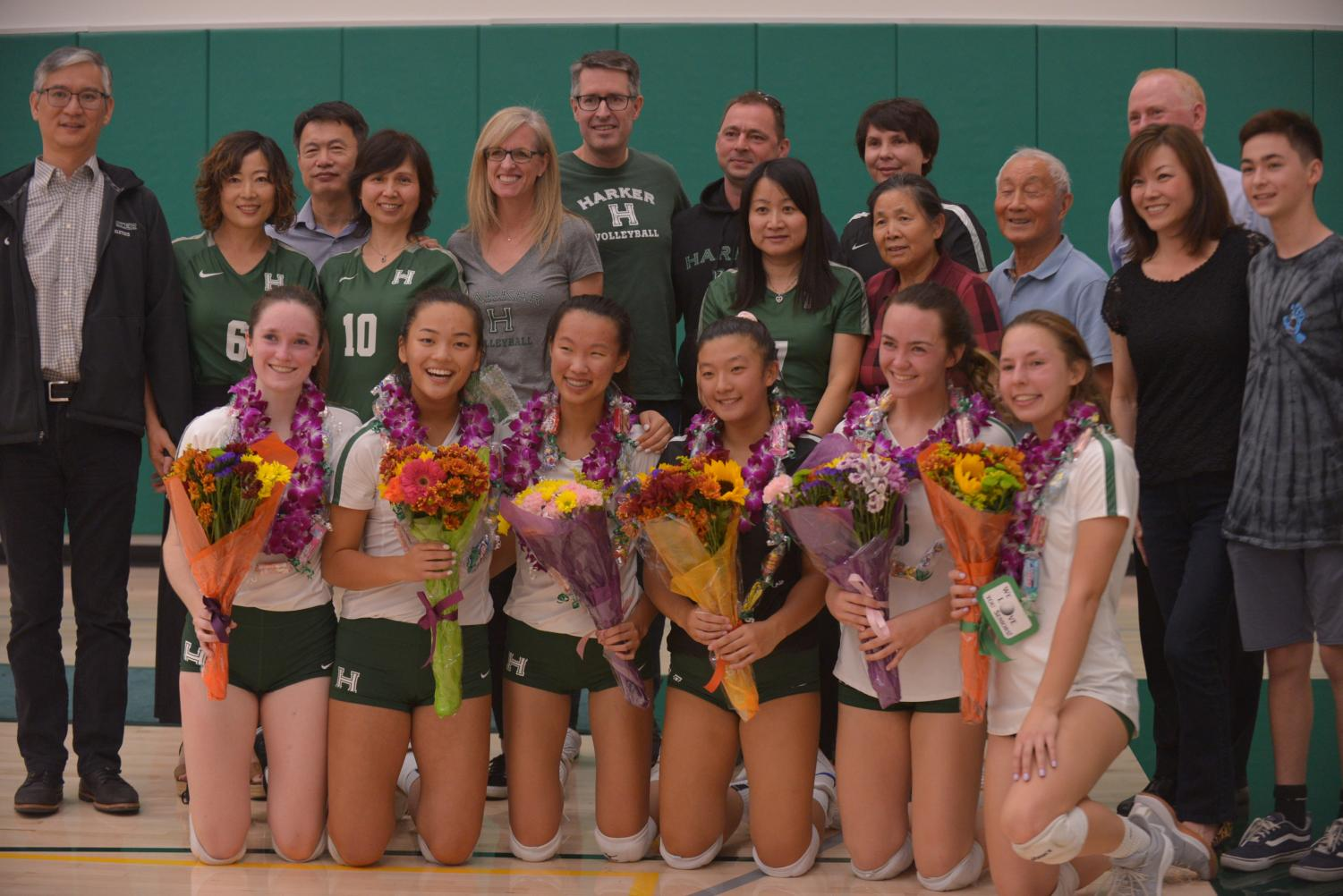 The seniors of the varsity volleyball team pose together with their families after the ceremony. This will be the girls' last home game this season, as they move on to compete in playoffs.