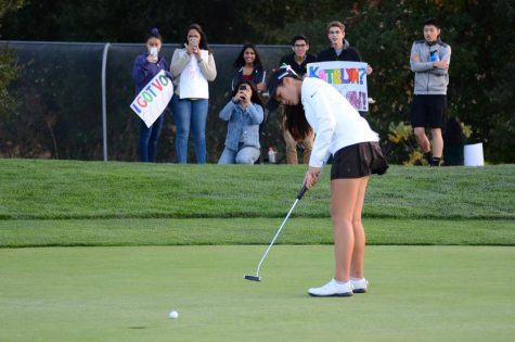 Katelyn Vo (12) watches the ball roll slowly across the green toward the last hole of the match. The only senior on the team, she was honored in the senior night ceremony following the match.