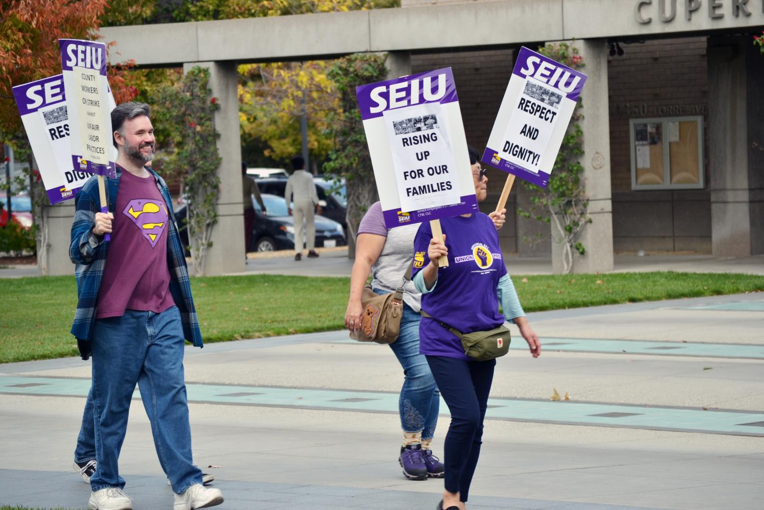 Carrying picket signs and wearing purple shirts that said