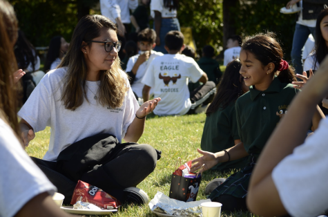 Maddie Hansen (10) converses with her Eagle Buddy over a lunch of burgers and chips on the Bucknall field. The class of 2022 traveled to the Bucknall campus to meet their Eagle Buddies for the first time yesterday.