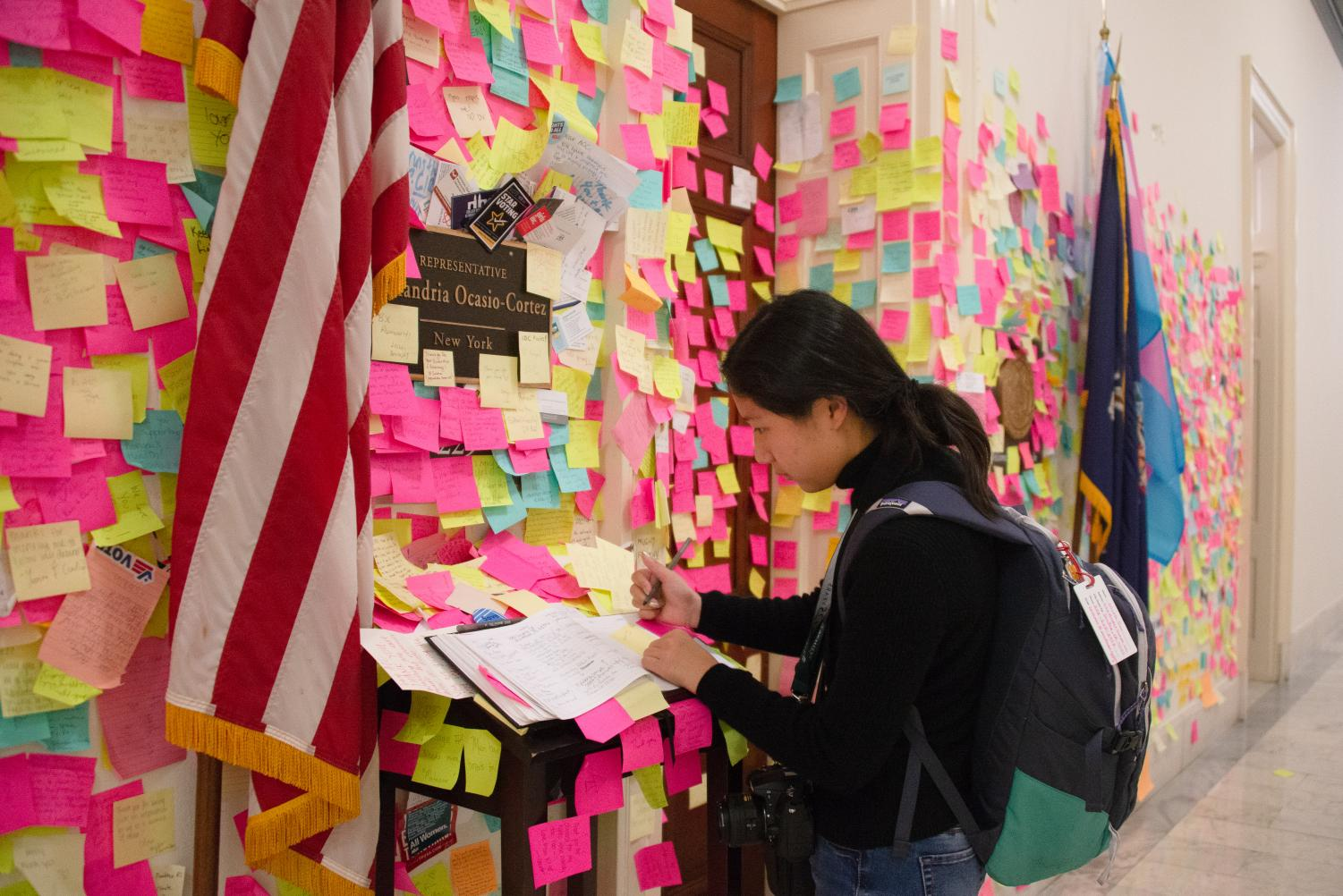 Nicole Tian (10) writes a message on a Post-It note to add to the mural of Post-Its around Rep. Alexandria Ocasio-Cortez's (D-NY) Cannon office door.