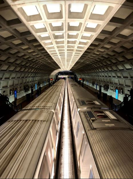 Subways on the red line of the D.C. Metro streak across after the latest stop at the Dupont Circle station. Each metro station consists of the same architectural structure: a wide arch filled with uniform square indentations.