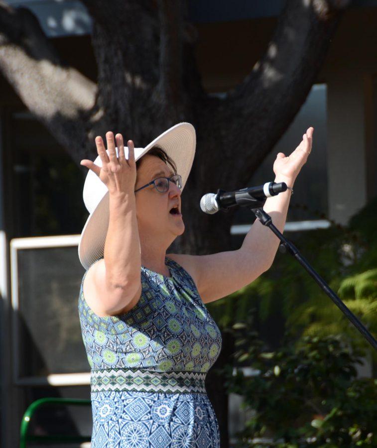 "English teacher Dr. Elizabeth Wahl raises her arms in the air as she sings George Gershwin's ""I Got Plenty o'Nuttin."""
