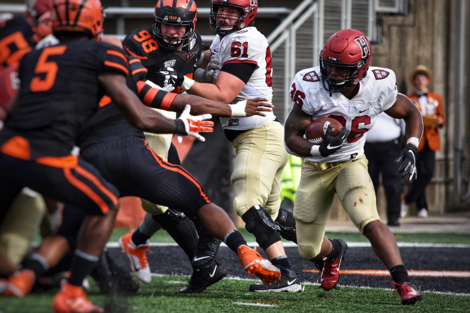 Harvard running back DeMarkes Stradford makes a move before carrying the ball past blockers on the line of scrimmage.