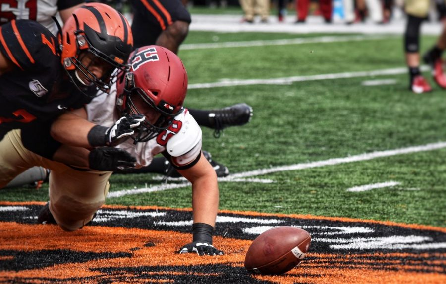 Princeton+linebacker+Daniel+Beard+battles+with+a+Harvard+player+to+recover+a+fumble.