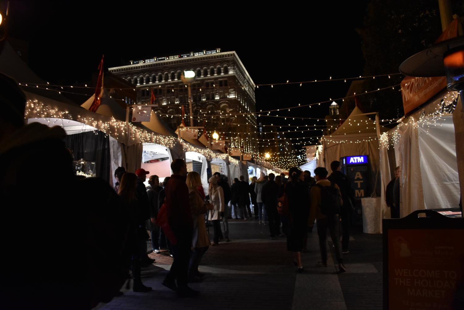 Customers walk through the sidewalk adjacent to Seventh Street. The Holiday Market opened yesterday and features local hand-crafted goods.