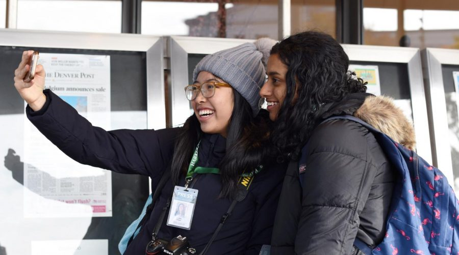 Winged Post Editor-in-Chief Gloria Zhang (12)  and Aquila Managing Editor Varsha Rammohan (11) take a  selfie in front of a display of newspapers on Nov. 20 outside of the Newseum. The Newseum, the only national museum dedicated solely to journalism, will be shut down as of Dec. 31, 2019.