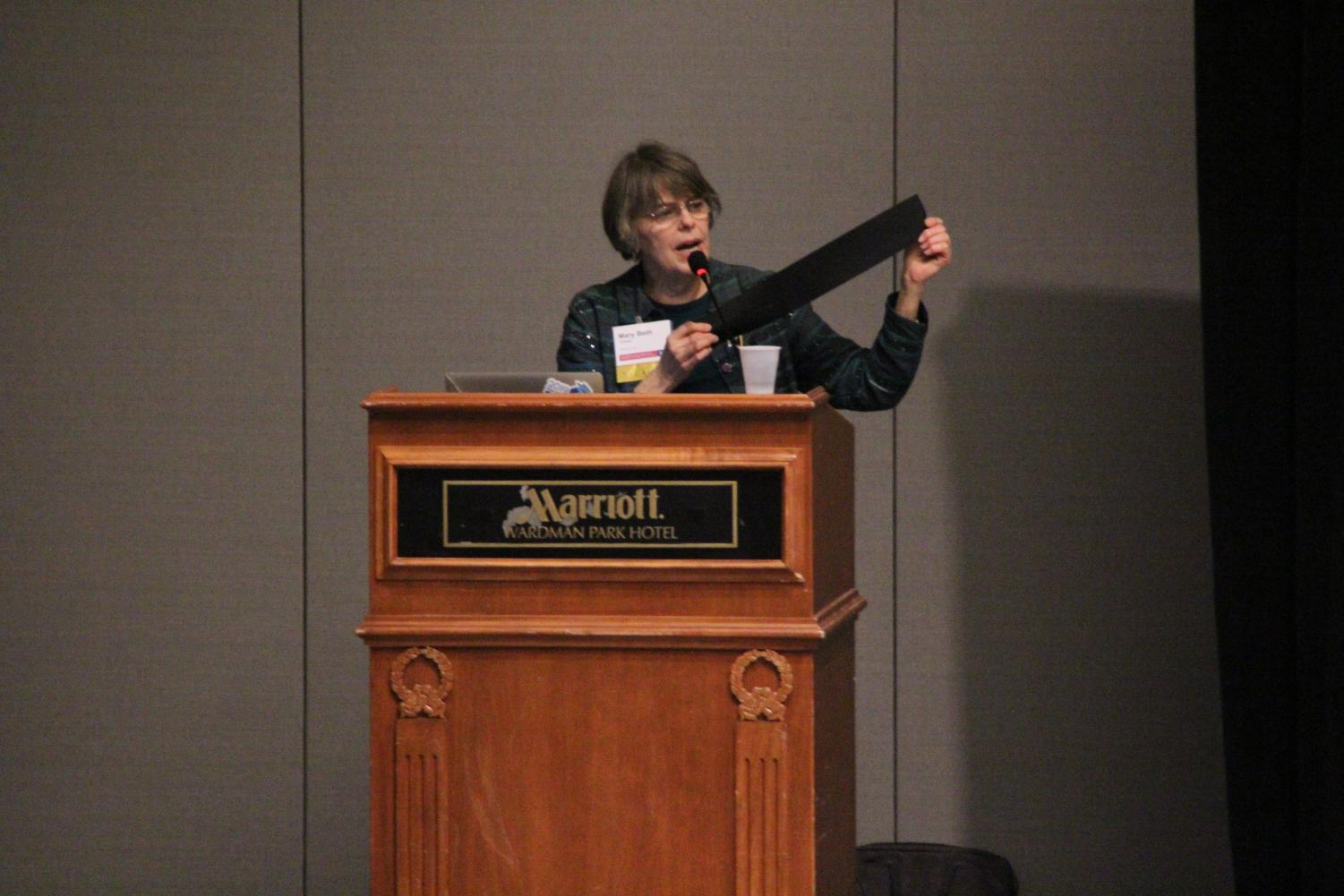Mary Beth Tinker holds up a signed black armband to an audience of student journalists at the JEA/NSPA convention, a similar piece to the original black armbands she wore to protest the resulting casualties of American involvement in the Vietnam War.