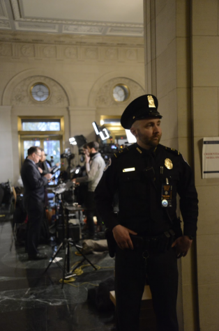 A security guard keeps watch while news anchors and reporters wait for updates behind him. More security measures were implemented in the building due to the impeachment hearings.
