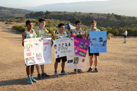 Seniors Nikhil Sharma, Grant Miner, Evan Cheng, Richard Hu and Martin Bourdev pose with their posters and candy-filled garlands. This meet was their final cross country meet of high school.