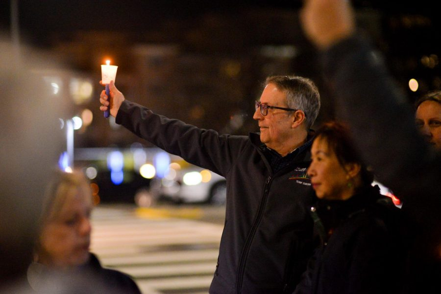 A demonstrator at a Cupertino pro-impeachment rally on Tuesday holds out an electric candle at cars turning onto Stevens Creek Boulevard. Hundreds of demonstrators gathered in various locations around the Bay Area to voice their support of the articles of impeachment, which the House voted to pass on Wednesday, making President Donald Trump the third ever U.S. president to be impeached.