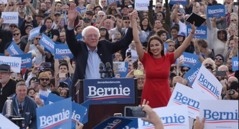 At the start of his speech, presidential candidate Sen. Bernie Sanders joins hands with Rep. Alexandria Ocasio-Cortez as the crowd shows their support. This rally was the conclusion of Sanders' campaign across Southern California over the past week.