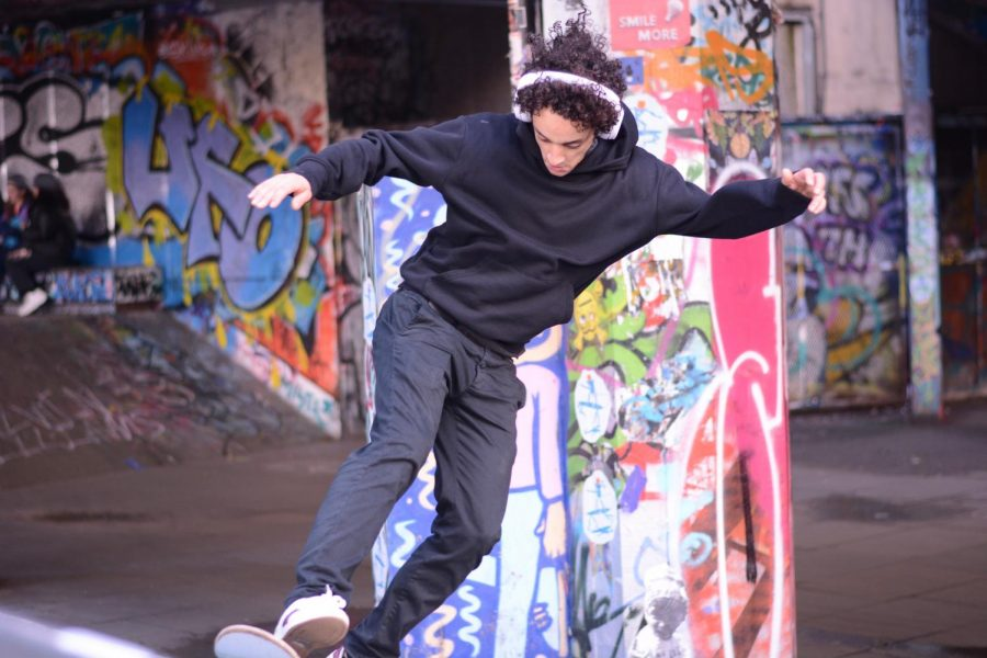 A man wearing headphones skates through the Southbank Skate Park in London, which is equipped with banks, ledgers and a set of stairs. The space is known as the home of British skating and has promoted creativity through street art.