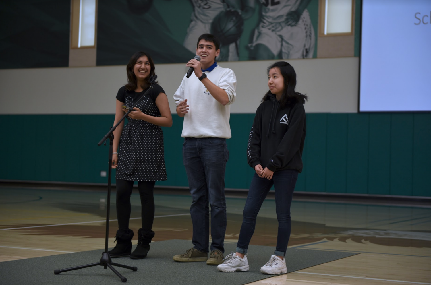 Presidents of the Chinese National Honor Society (CNHS), French National Honor Society (FNHS) and Japanese National Honor Society (JNHS) Sana Pandey (12), Grant Miner (12) and Katie Chang (12), respectively from left to right, announce the three club's upcoming shared club week. The three clubs will take turns selling cultural snacks during lunch and after school this week.