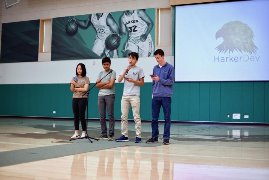 The four Harker Dev admins, Gloria Zhu (10), Chirag Kaushik (10), Ben- nett Liu (12) and John Lynch (11), give an announcement at school meeting. They  presented their new developments, including a platform to streamline announcements.