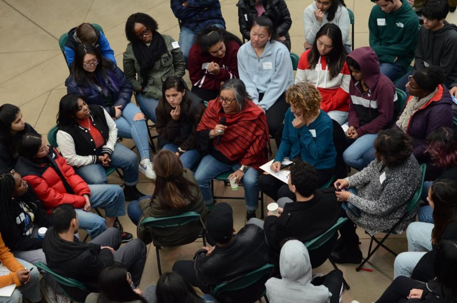 "Attendees at the second annual Student Diversity Leadership Gathering participate in the fishbowl activity. In the ""fishbowl activity,"" chairs were set up in the center of the room with people of color in the middle and white people forming a ring around them. Featured speaker and organizer Dr. Rodney Glasgow showed three videos to prompt discussion."