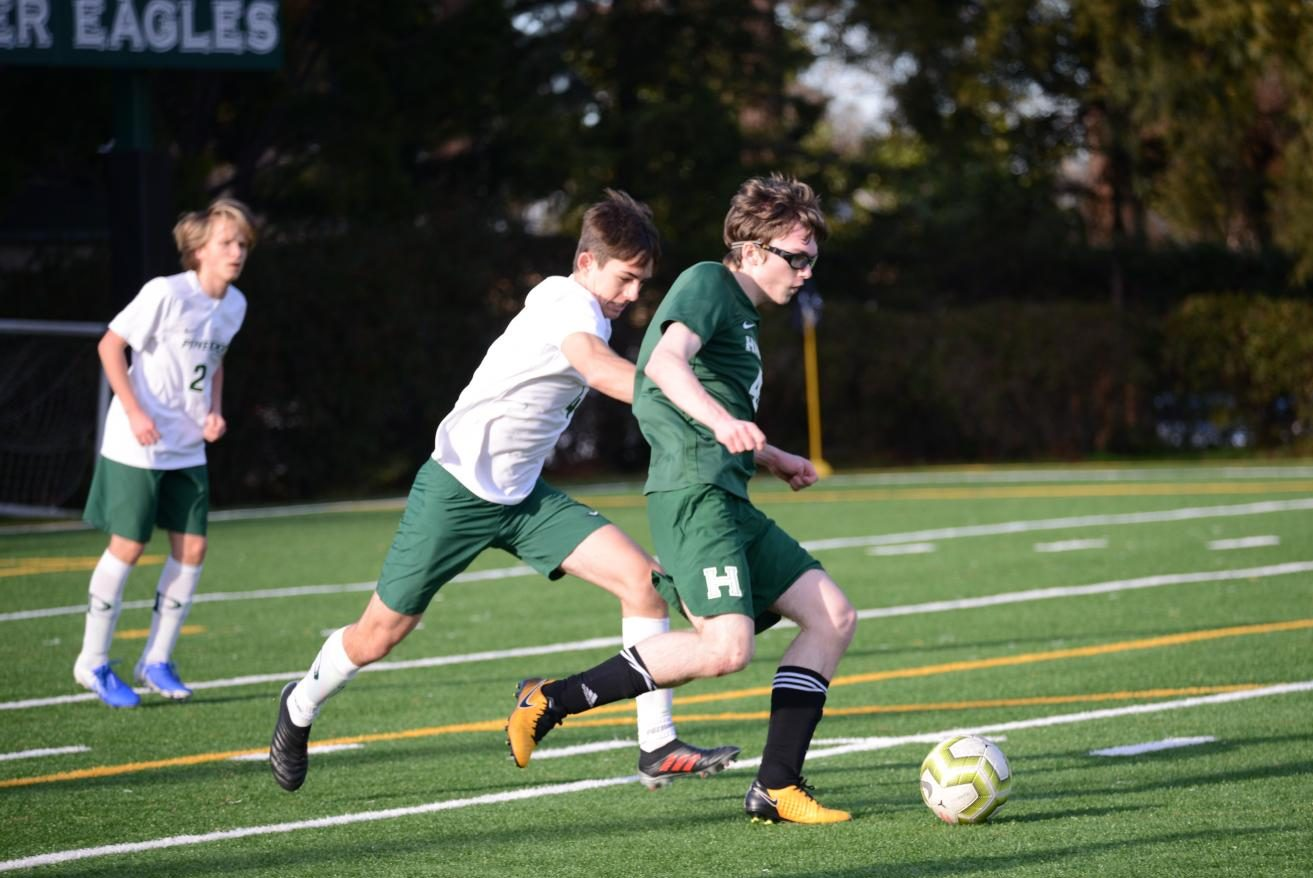JV player Anton Novikov (11) fights to possess the ball from a Pinewood player during the annual Kicks Against Cancer event.