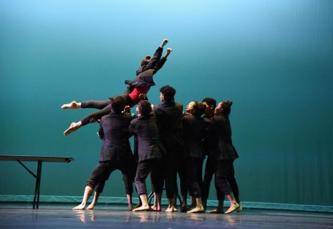Junior Zoe Kister jumps into a crowd of dancers. Zoe is one of eight student choreographers.