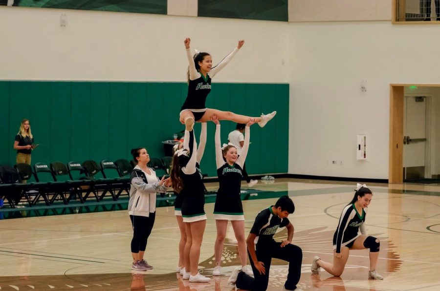 """Members of the varsity cheer squad perform during halftime of the varsity boys basketball game last Thursday. """"It was a little rough, we definitely could have played better,"""" Emma Crook (10), a member of varsity cheer, said."""