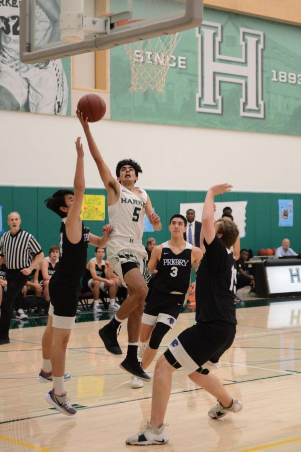 Arjun Virmani (11) attempts a driving layup amidst multiple Priory defenders during the senior night matchup last Tuesday. The boys varsity basketball team will host Design Tech on Friday at 4 p.m. for the first round of CCS playoffs.