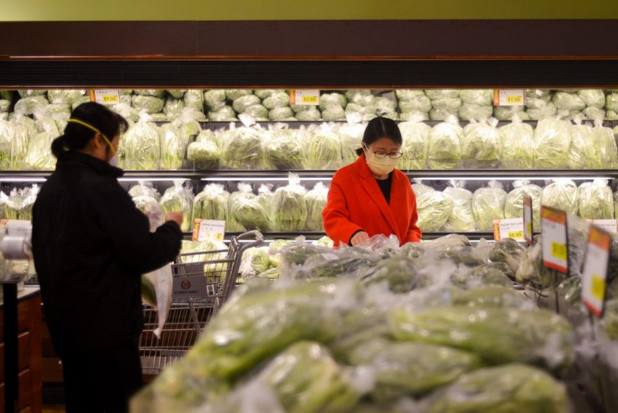 Two women, both wearing protective masks, select vegetables at 99 Ranch Market in Cupertino on Sunday evening. Due to the global novel coronavirus outbreak and the recent confirmation of cases in Santa Clara County, stores around the Bay Area have been experiencing shortages of masks.