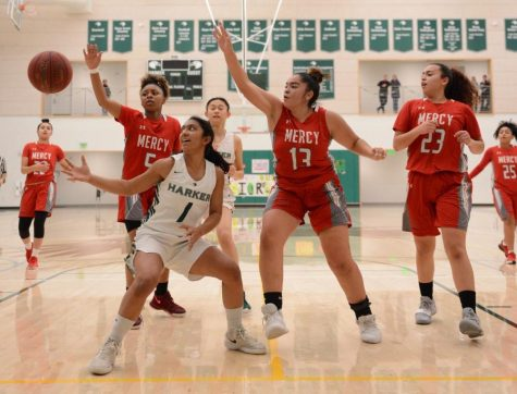 Co-captain Maria Vazhaeparambil (11), surrounded by three Mercy defenders, reaches for a loose ball during the first quarter of the Eagles' matchup last Friday. The girls started off evenly, tied 27-27 heading into the locker room at halftime.