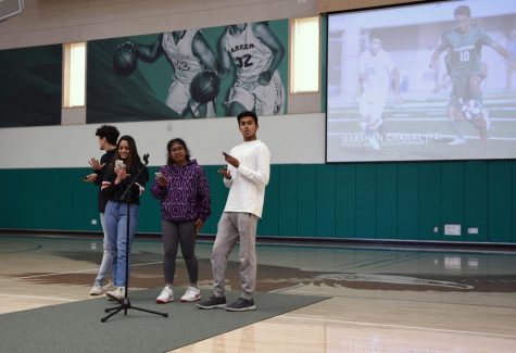 Giovanni Rofa (12), Meona Khetrapal (11), Rohan Varma (11) and Adhya Hoskote (12) deliver the Eagle Update during Tuesday's school meeting. They reviewed the results from recent games played by the girls basketball, girls soccer, boys basketball and girls basketball.