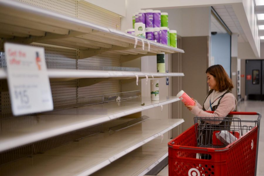 Browsing nearly empty shelves, a customer shops for surface wipes at Target in the Westgate Center. Stores like Target and Costco have been running low on hygiene products in the past week as local residents stock up on essential supplies to prepare for a potential COVID-19 outbreak.