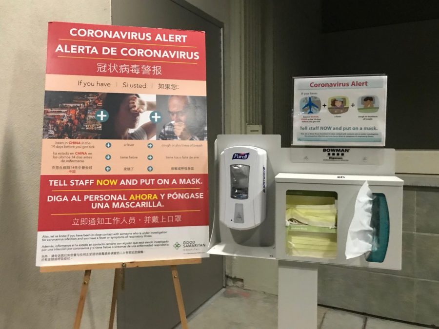A warning sign with information about coronavirus and a station with hand sanitizer, tissues and face masks stand outside the entrance doors to the emergency room of Good Samaritan Hospital in San Jose, CA. As of March 2, there are 9 confirmed cases of COVID-19 in Santa Clara County.