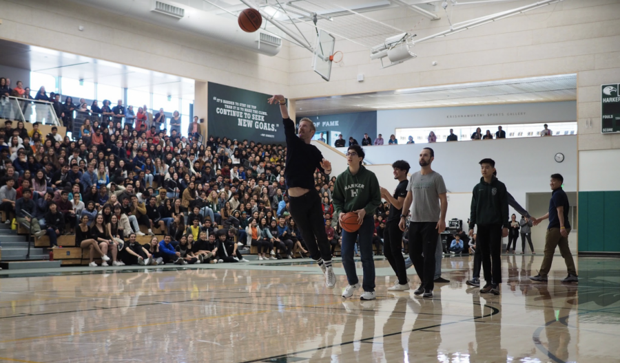Senior class dean Karl Kuehn takes a shot at the basket during the knock out game at last Friday's school meeting. In the game, students from all grade levels and faculty members competed for a bag of gummy worms.