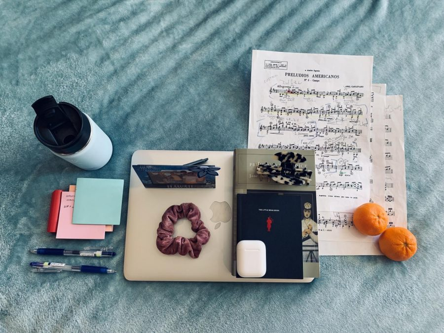 My pandemic kit lays strewn across a fuzzy blue blanket. Among my necessary items are post-its, my AirPods, my music and coffee.