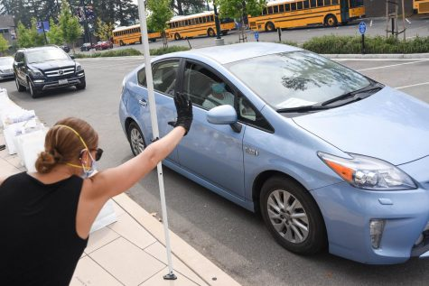Upper school librarian Meredith Cranston waves to a student driving by. Students drove by the front loading zone on Saturday to receive supplies for the upcoming school year.