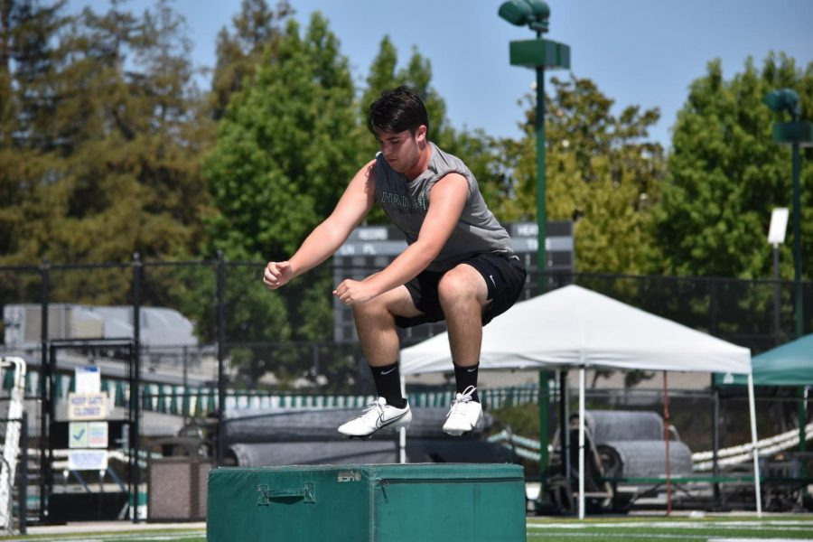 Marcus Anderson (12) performs a box jump at a workout hosted on Davis Field during summer break. Box jumps are an effective exercise for strengthening the lower body, increasing one's vertical jump. and improving athletic explosiveness overall.