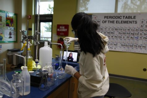 Nilisha Baid (12) pours out the contents of a volumetric flask into a sink during an experiment as her lab partner, Vaishnavi Murari (12), looks on via Zoom. Six out of the seven students in Honors Analytical Chemistry participated in the Nov. 21 in-person lab.