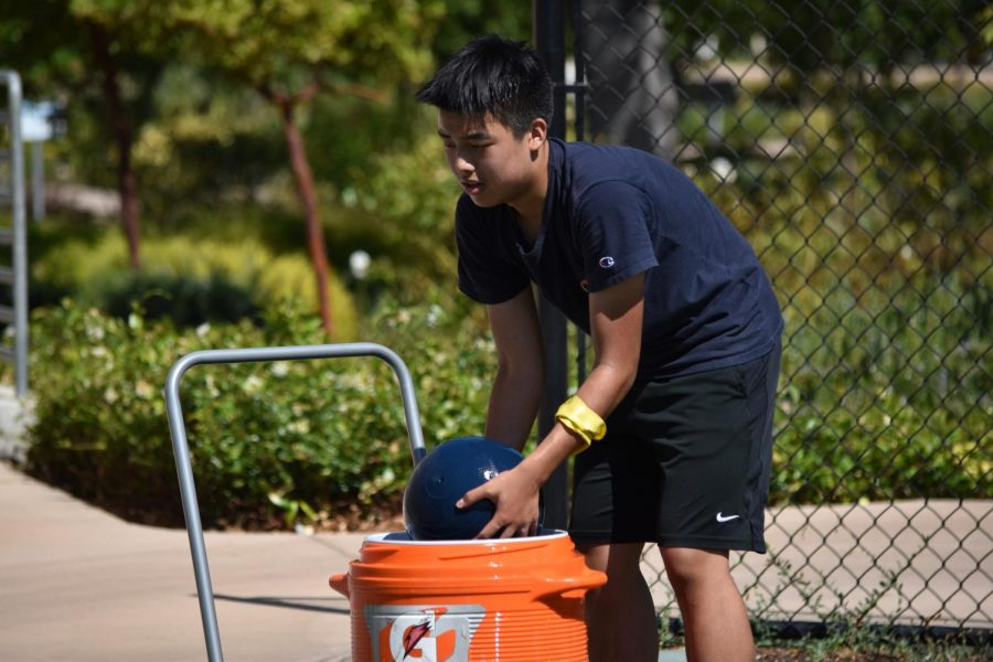 Daniel Lin (9) cleans a weight ball in a water cooler after a workout. In order to reduce spread of COVID-19, all equipment must be cleaned after workouts before being used again.