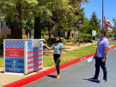 Two Santa Clara County Registrar of Voters staff stand in front of a ballot drop box.
