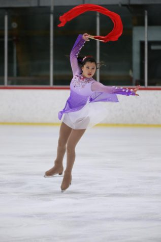 Alice Feng (11) performs her skate routine with a flowing red fan as a prop. Her bejeweled dress recalls elements of Chinese culture, an inspiration to the routine.