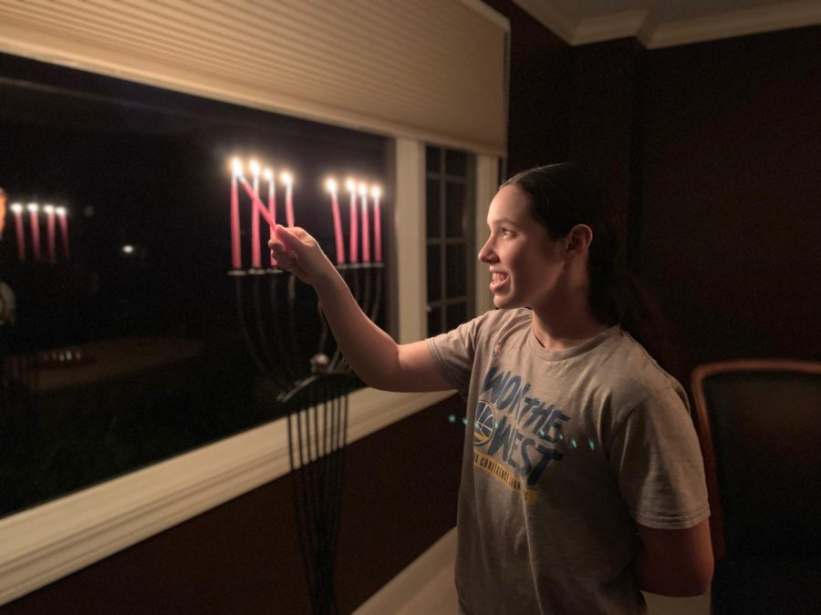 Ellis Goldman (12), who celebrates Hanukkah lights a candle on the menorah. The candles of the menorah are lit from right to left, with the shamash burning brightly in the center each night.